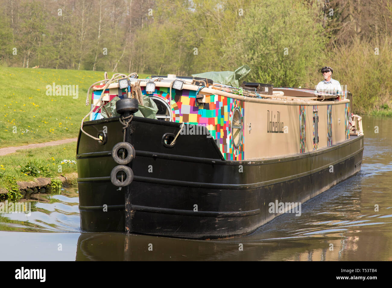 Landscape, close up of oncoming narrowboat travelling on UK canal in spring sunshine; single, retired man in cap stands at rear steering canal boat. - Stock Image