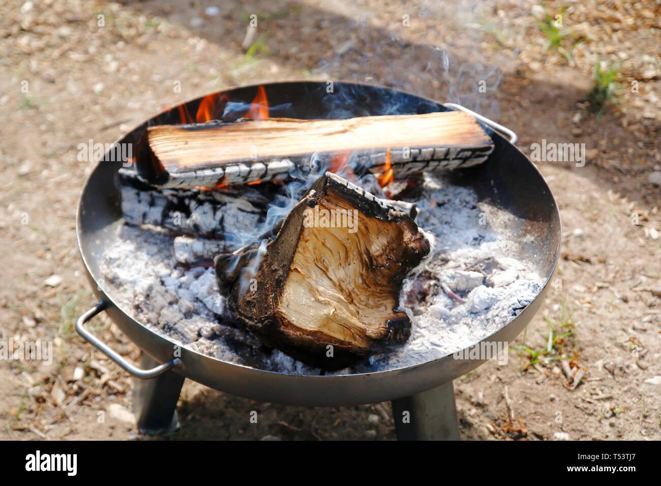 Feuer in einer Feuerschale, großer Holzgrill mit Asche - Stock Image