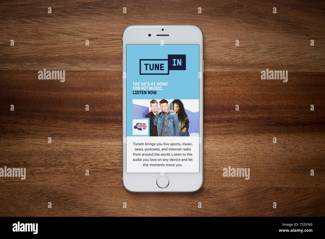 An iPhone showing the Tune In website rests on a plain wooden table (Editorial use only). - Stock Image