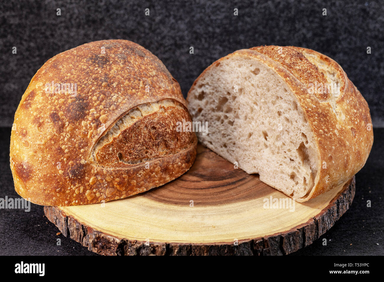 Artisan loaf of traditional Homemade sourdough focaccia Boule bread with crust on a wooden board - Image Stock Photo