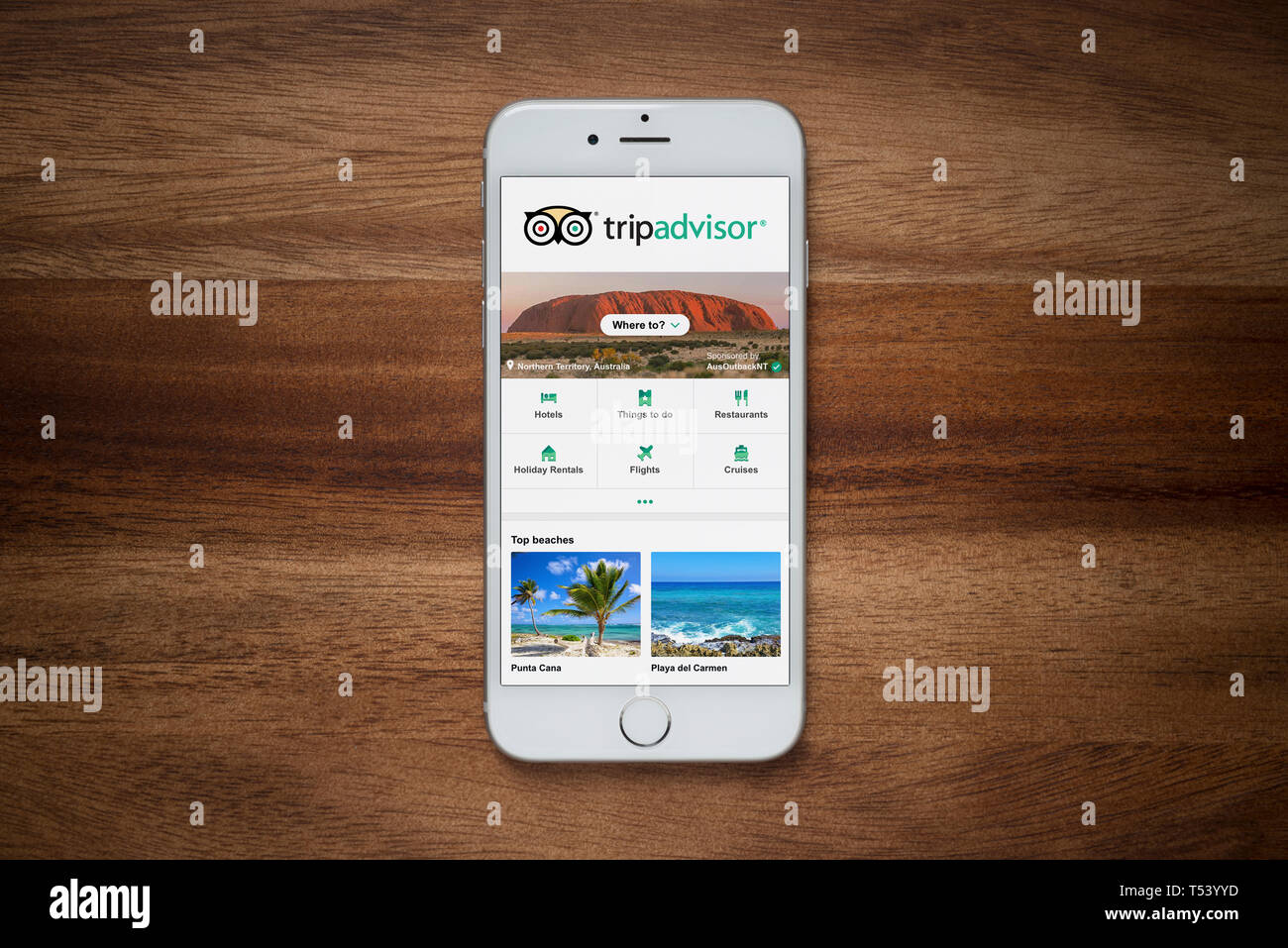 An iPhone showing the Trip Advisor website rests on a plain wooden table (Editorial use only). - Stock Image