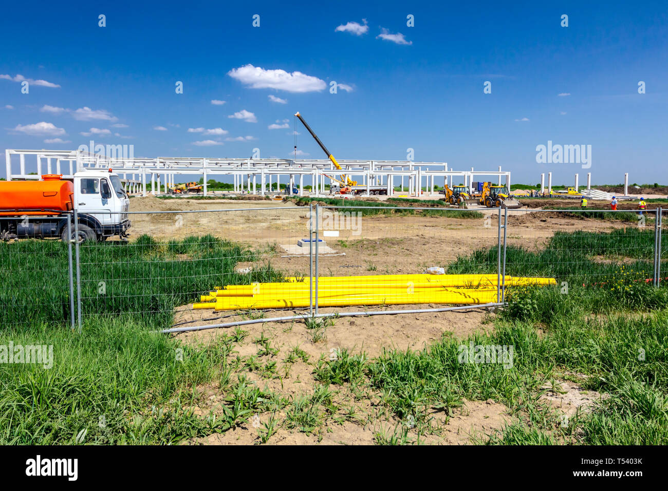 Landscape transform into urban area with machinery, people are working on unfinished modern edifice. View on construction site. Stock Photo