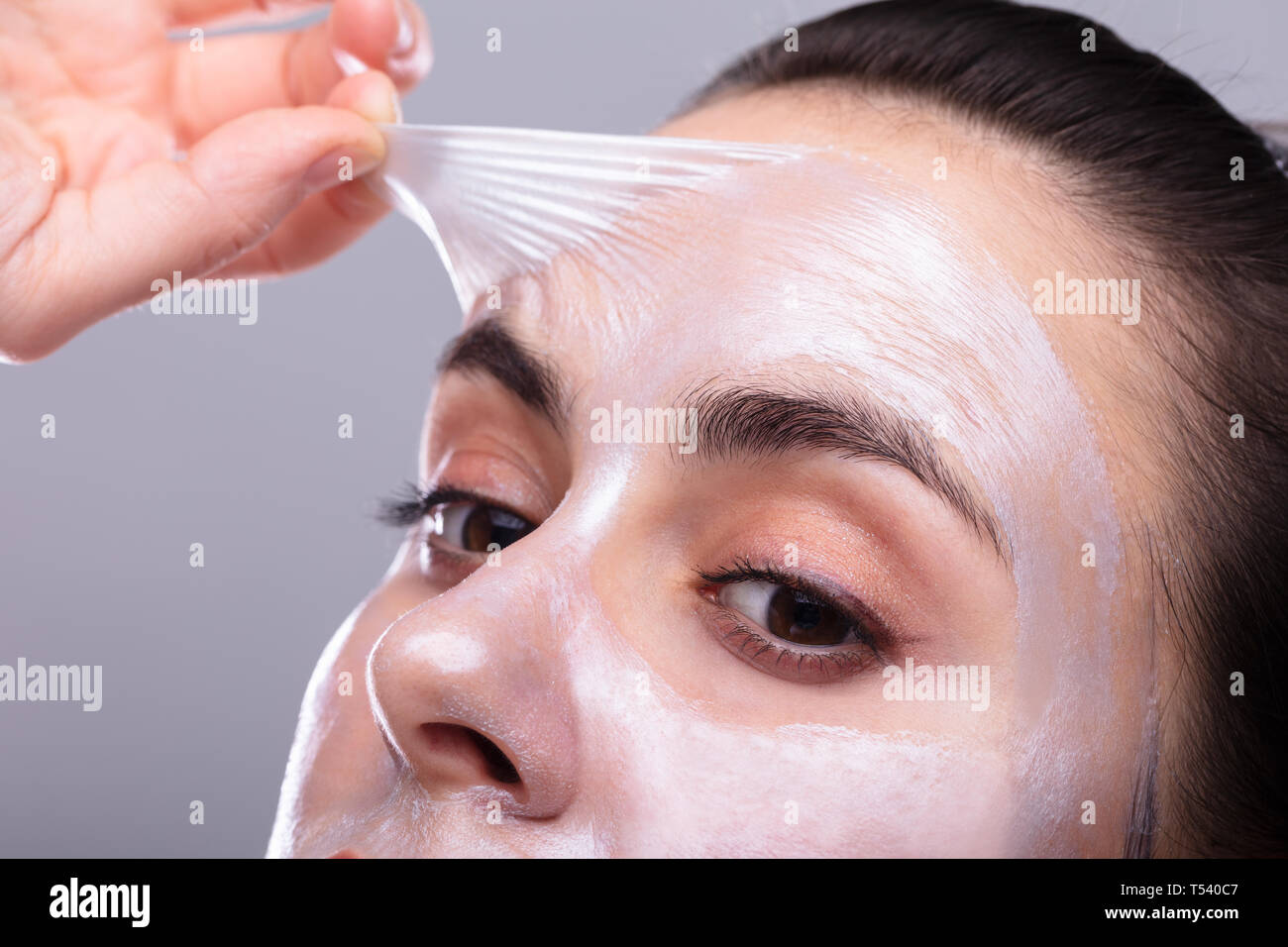 Portrait Of A Beautiful Young Woman Removing Peeling Mask From Her Face Stock Photo
