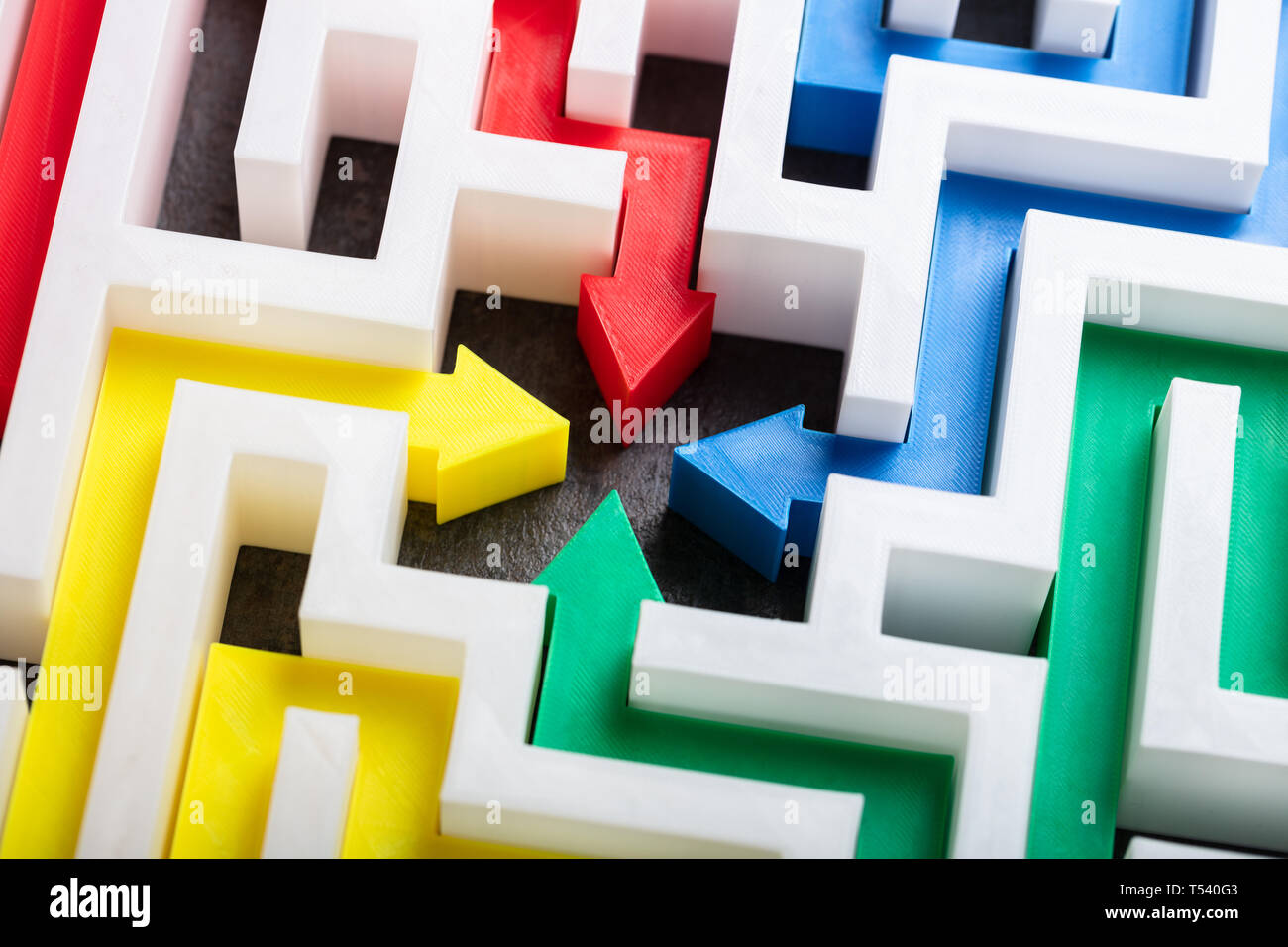 An Elevated View Of Multi Colored Arrows In The Center Of White Maze - Stock Image