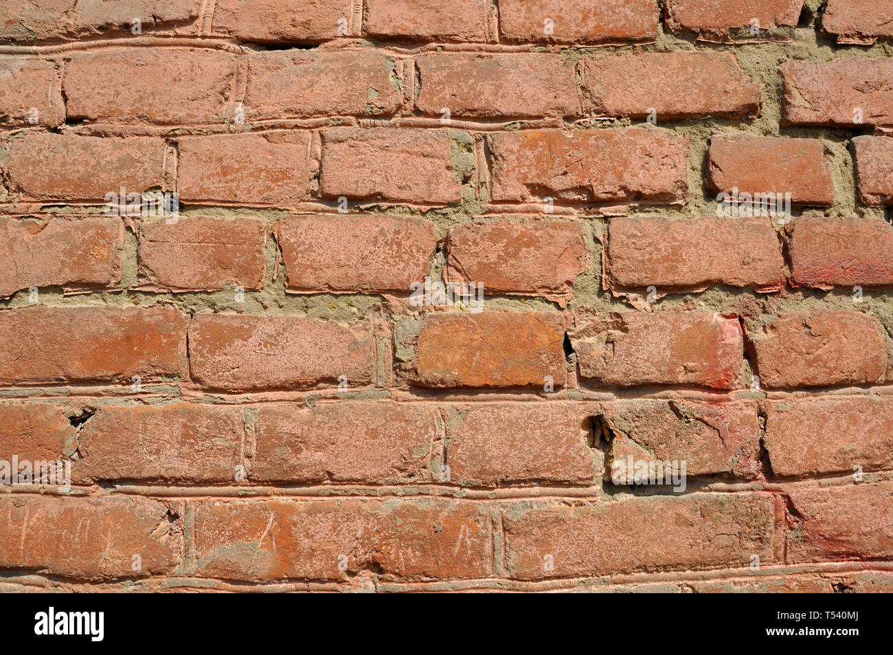 Old flaky red brick wall with cracks and scratches - Stock Image