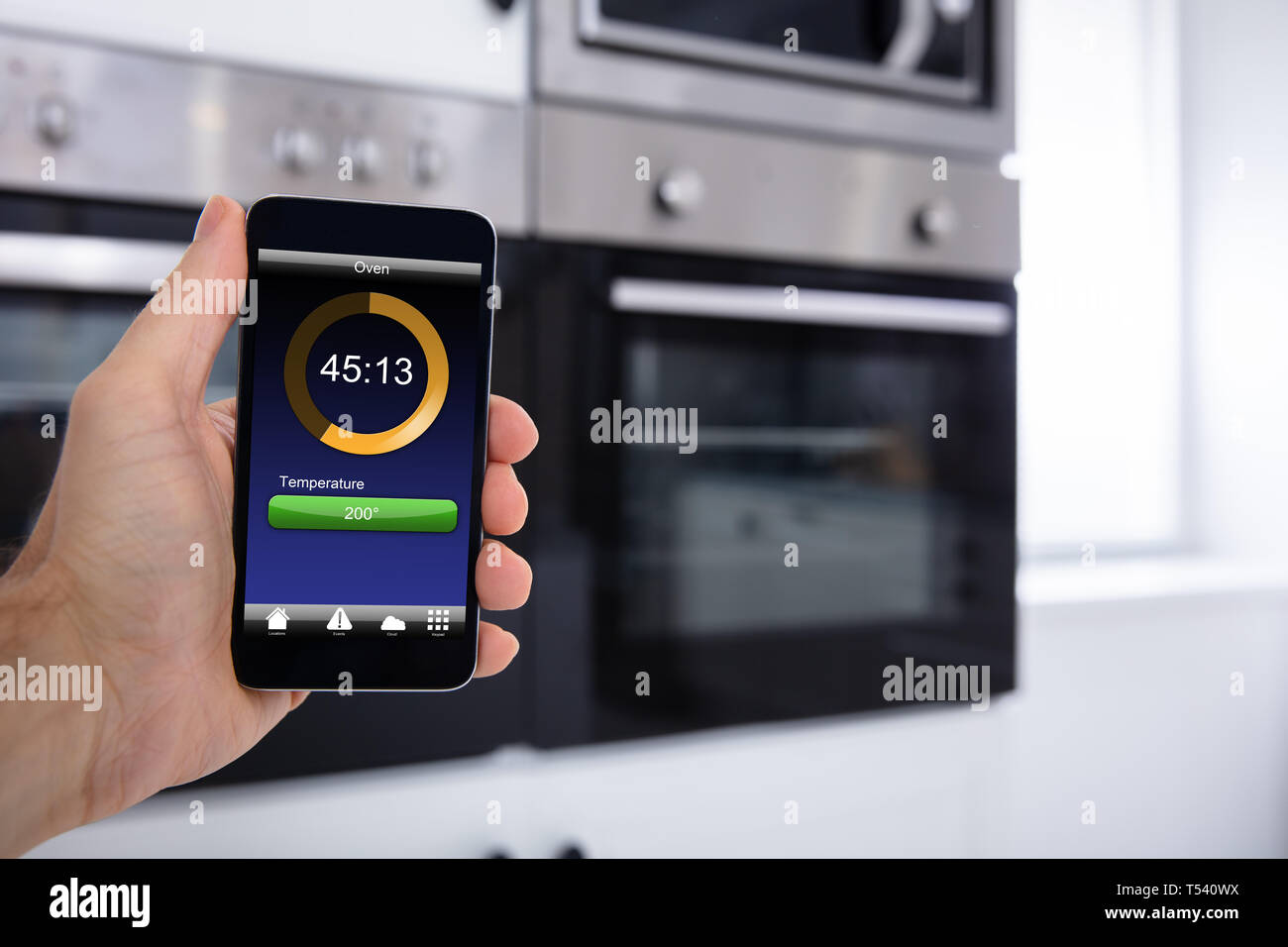Close-up Of A Person Hands Operating Oven Application With Cellphone - Stock Image
