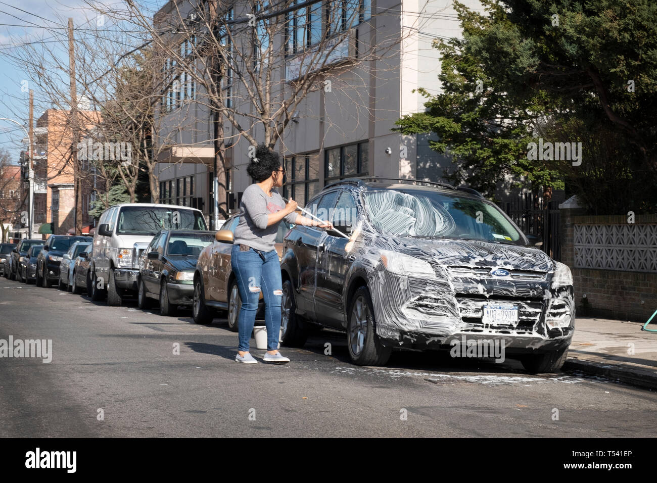 A woman washing her SUV with soap and water on a side street in Corona, Queens, New York City Stock Photo