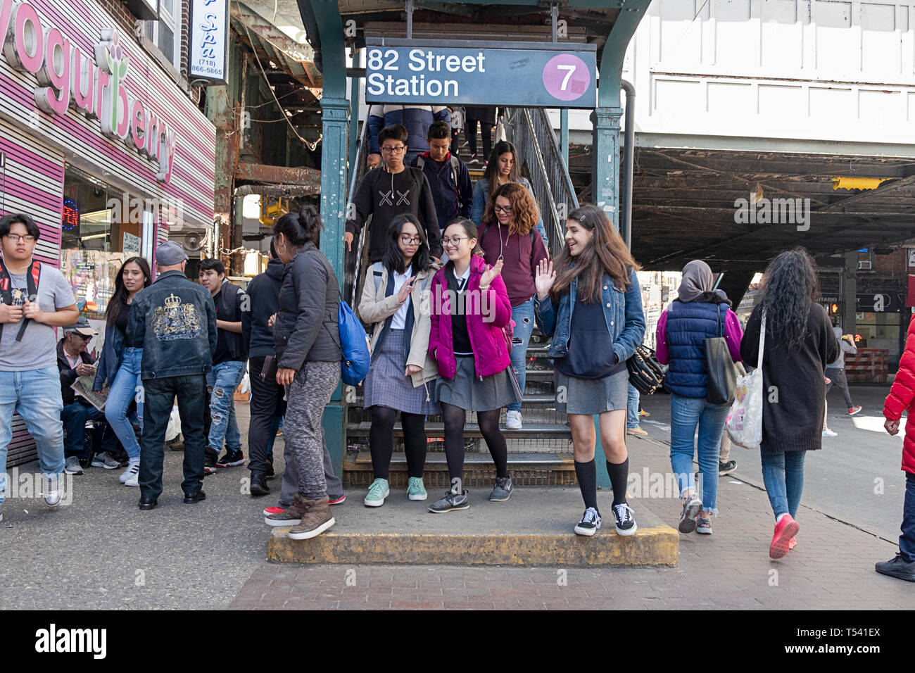 Teenage students returning from school and others emerge from the 7 train on 82nd Street in Jackson Heights, Queens, New York City Stock Photo
