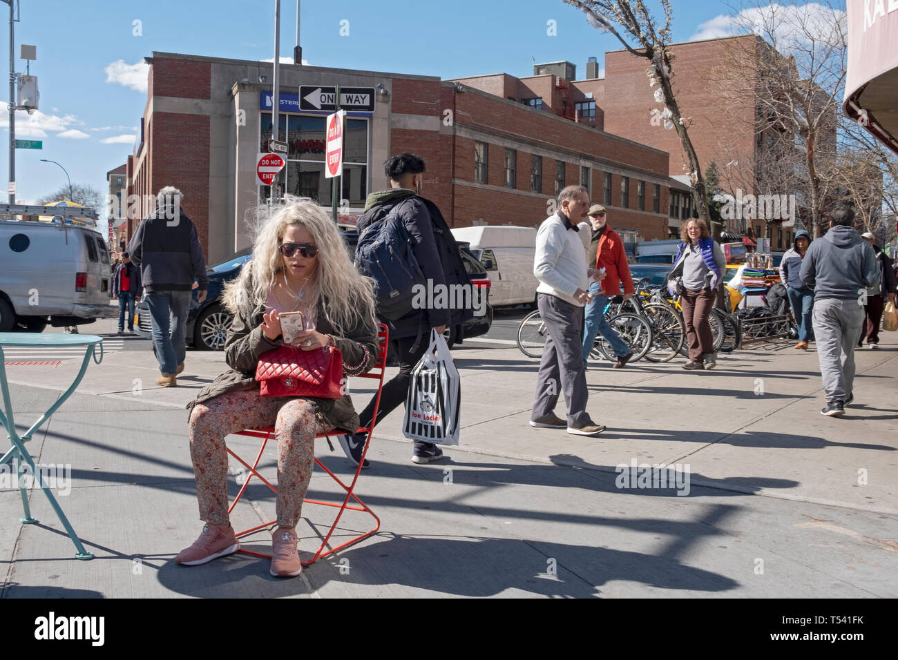 A street scene featuring a seated woman with long blond hair texting on her cell phone. In Jackson Heights, Queens, New York City. Stock Photo