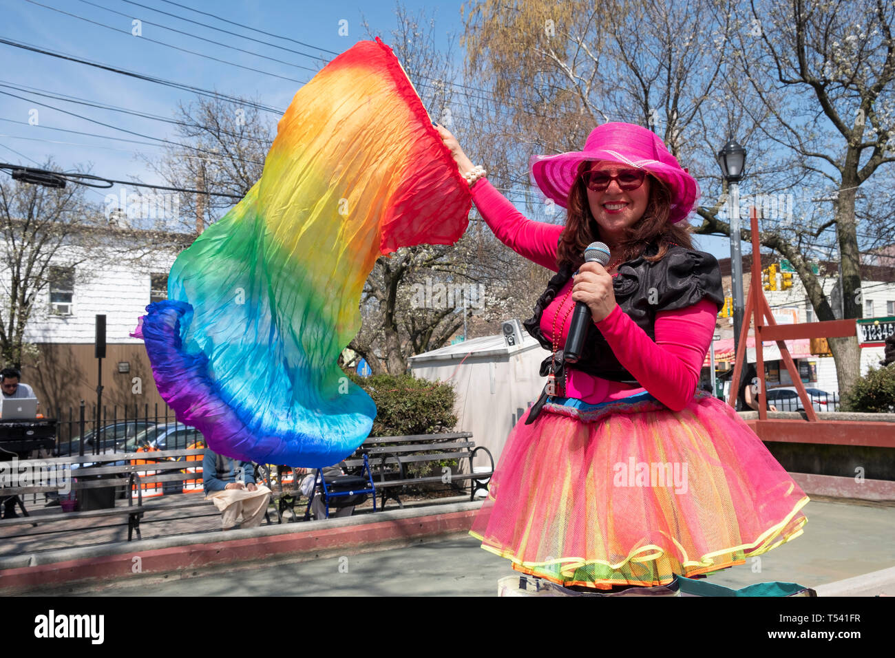 A Hispanic American woman in a colorful costume MCing an Easter party in a park in Corona, Queens, New York City. Stock Photo