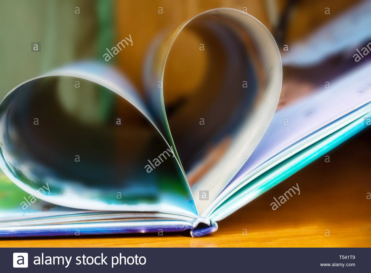 The blurring of the book opens on the desk, the pages rolls together to form a heart, shallow depth - Stock Image