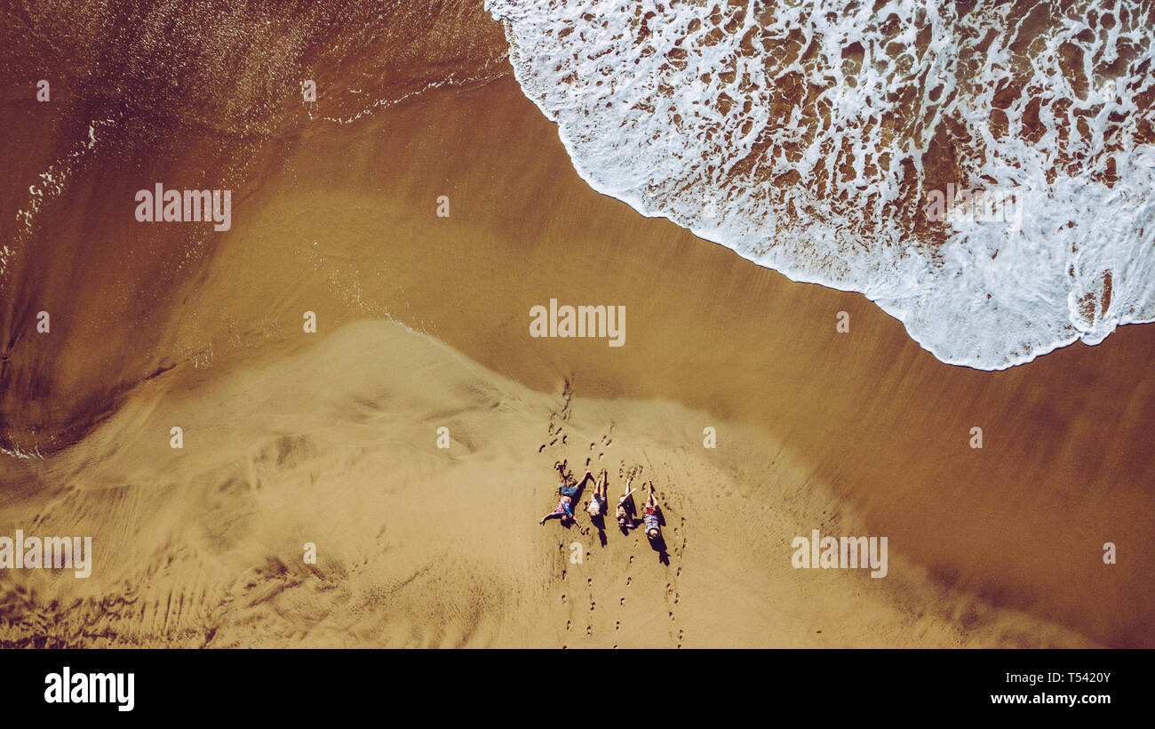 Group of friends people enjoying the beach laying on the sand - aerial top view with waves comnig, summer vacation travel lifestyle for young men and  Stock Photo