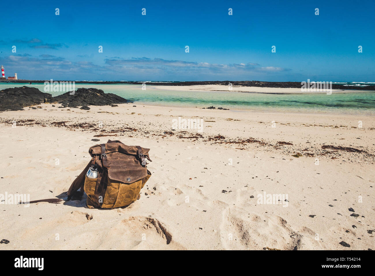 Vintage beautiful leather backpack at the beach for travel summer holiday vacation concept - tropical sand and blue background Stock Photo