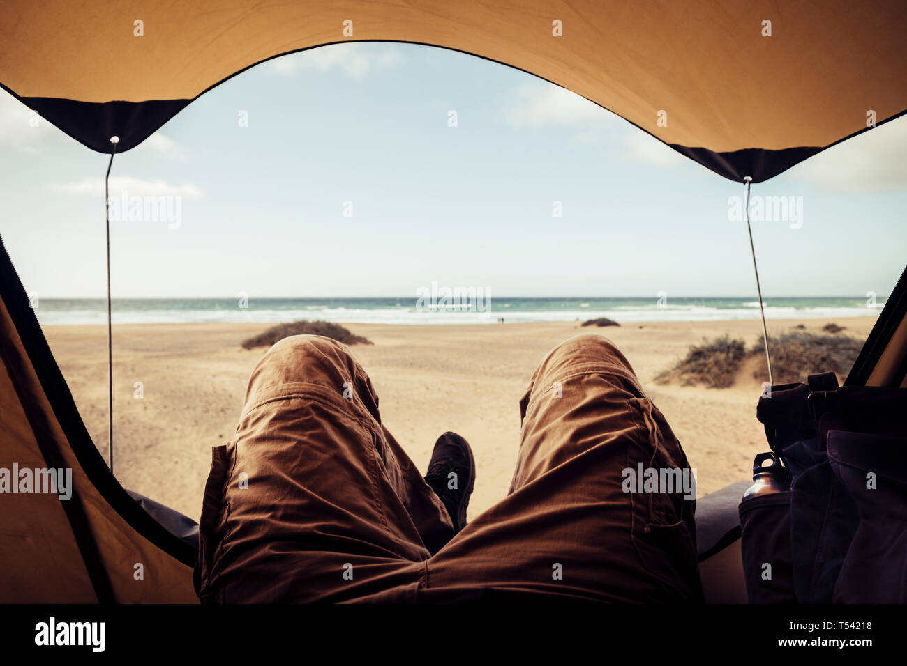 Alternative vacation concept with man in trekking clothes laying outside the tent campiing free at the beach looking the ocean horizon and enjoying th Stock Photo