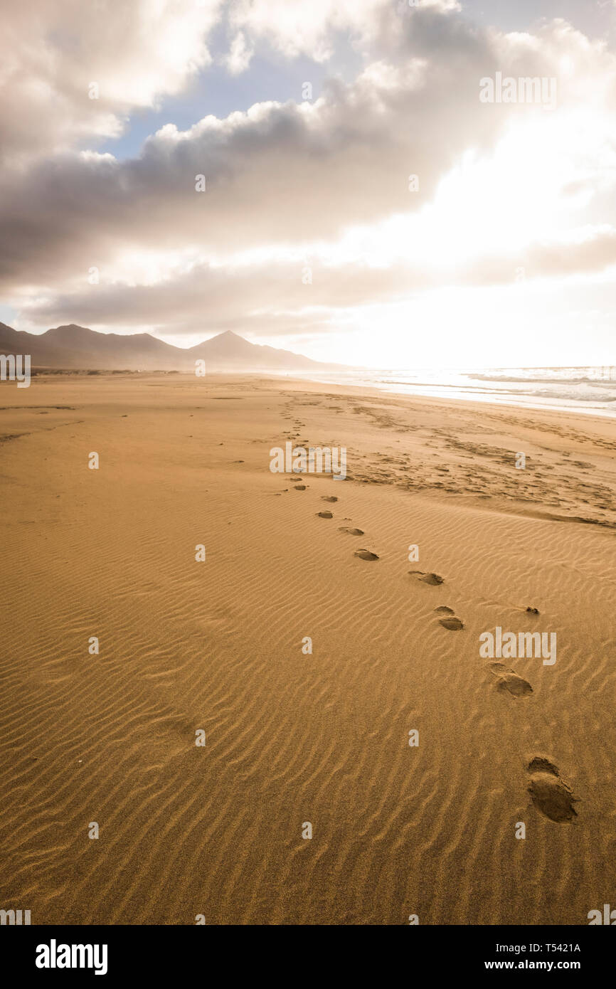 Footprint at the beach for explore in wild scenic place concept during alternative tourism vacation - dramatic cloudy sky and mountains in background  Stock Photo