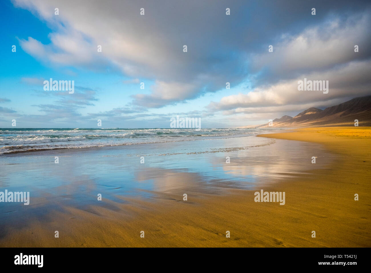 Lonely beach coloured and reflected with beautiful mountain background  with cloudy sky - summer tropical vacation concept in free sandy scenic place  Stock Photo