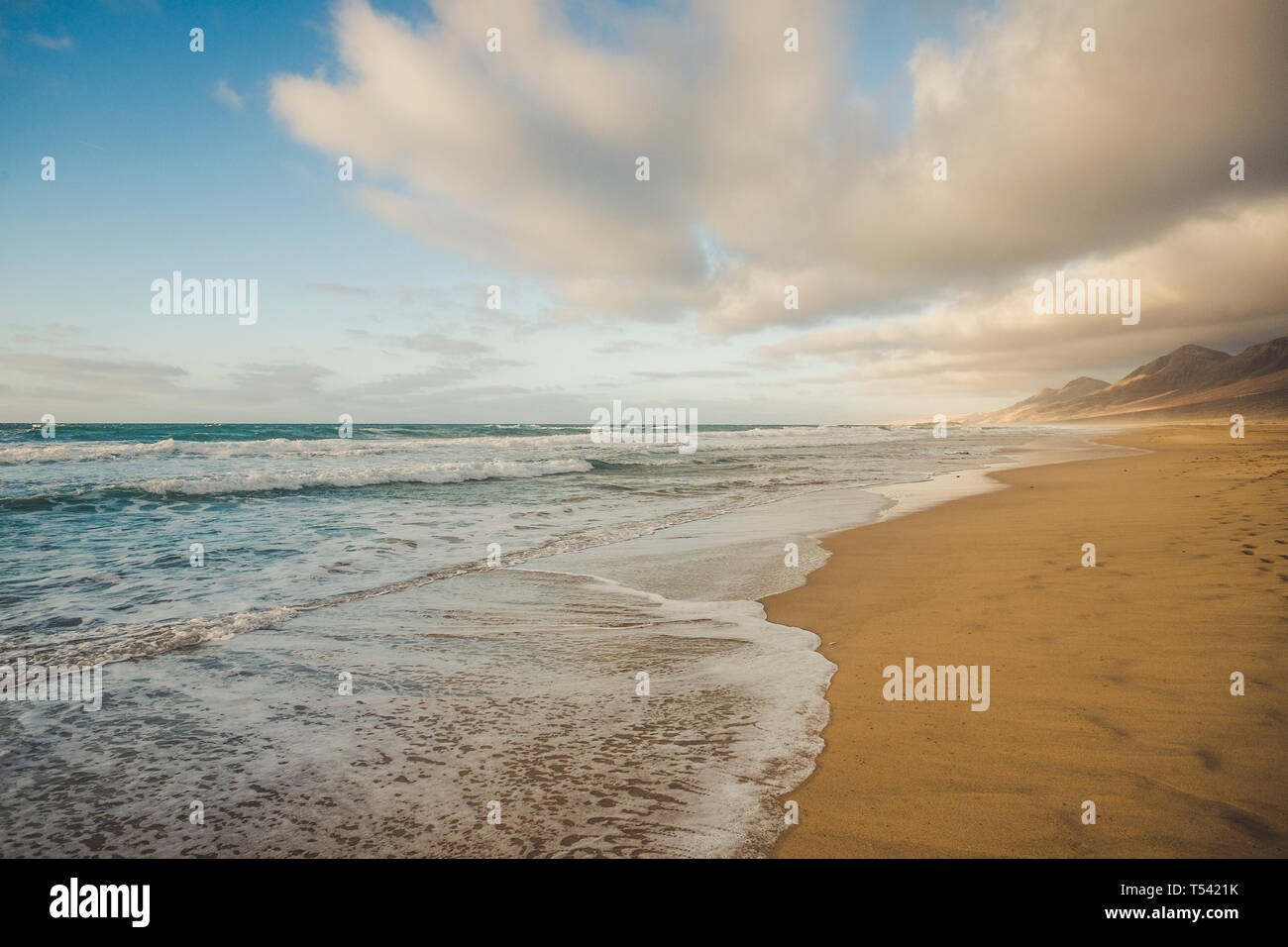 Lonely beach with beautiful mountain background  with cloudy sky - summer tropical vacation concept in free sandy scenic place with nobody there Stock Photo