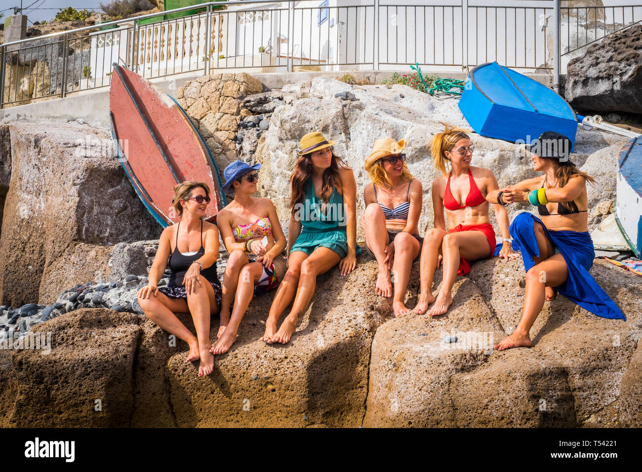 group of nice and beautiful friends smiling together having fun in friendship summer leisure time outdoor near the beach. squimsuits and ladies enjoye Stock Photo