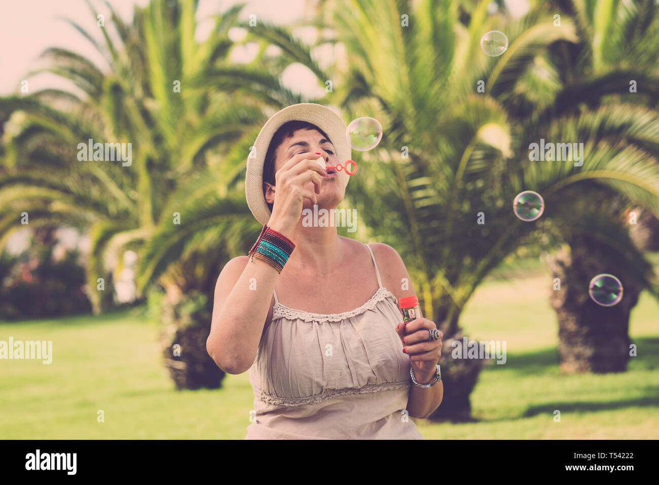Young cute caucasian female play and have fun doing soap bubbles outdoor at the tropical park - enjoying leisure activity with kid play - no stress pe Stock Photo