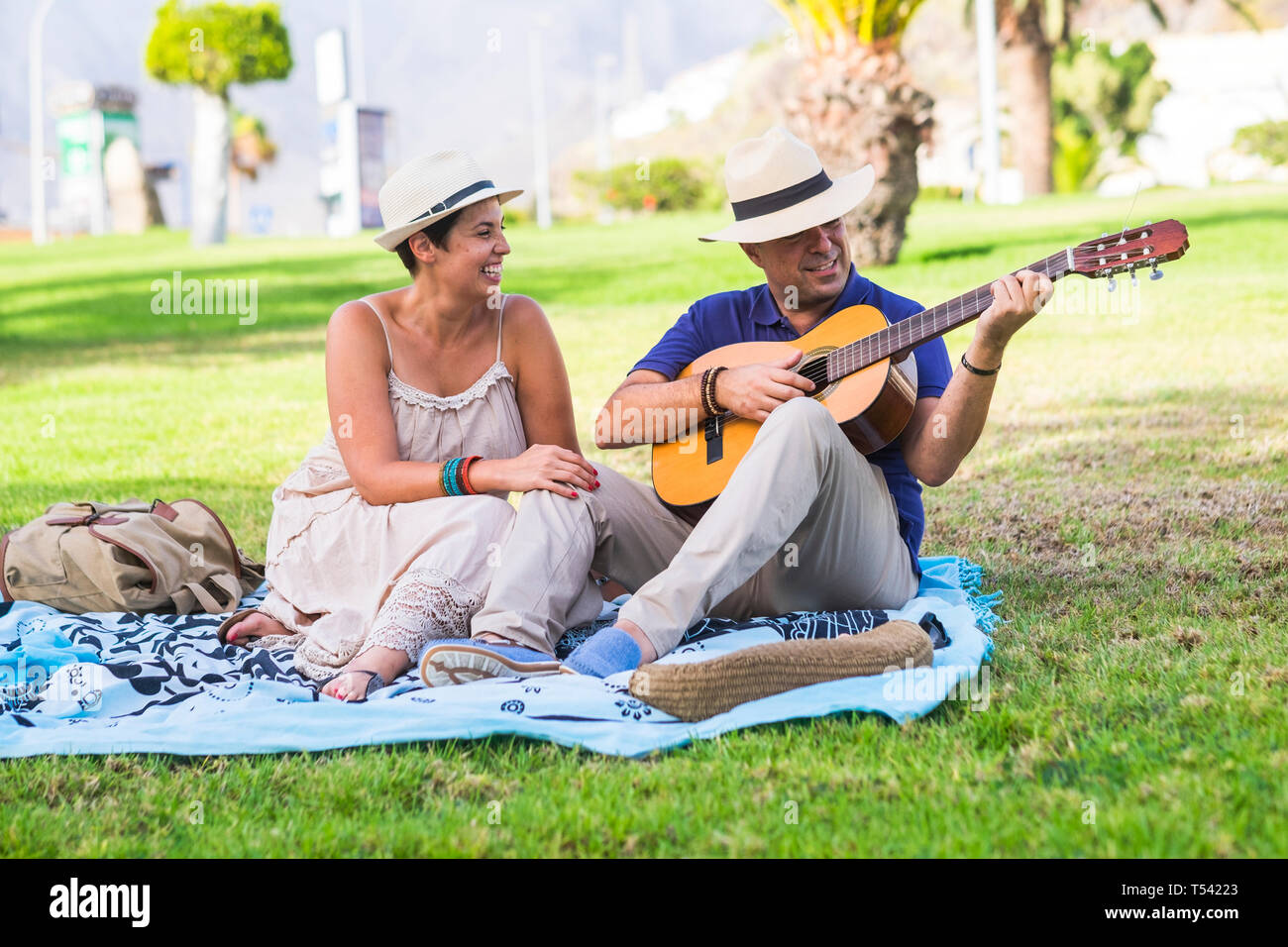 Romantic happy nice caucasian couple people playing a guitar for romantic activity sitting on a meadow in outdoor nature park together - love and rela Stock Photo