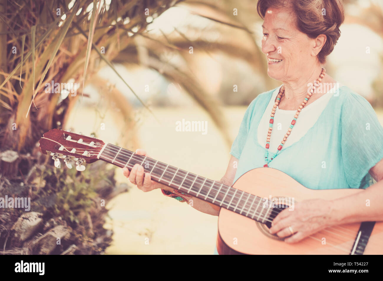 Senior caucasian beautiful cheerful happy lady adult people singing a guitar outdoor enjoying the leisure activity - third age silver society concept  Stock Photo