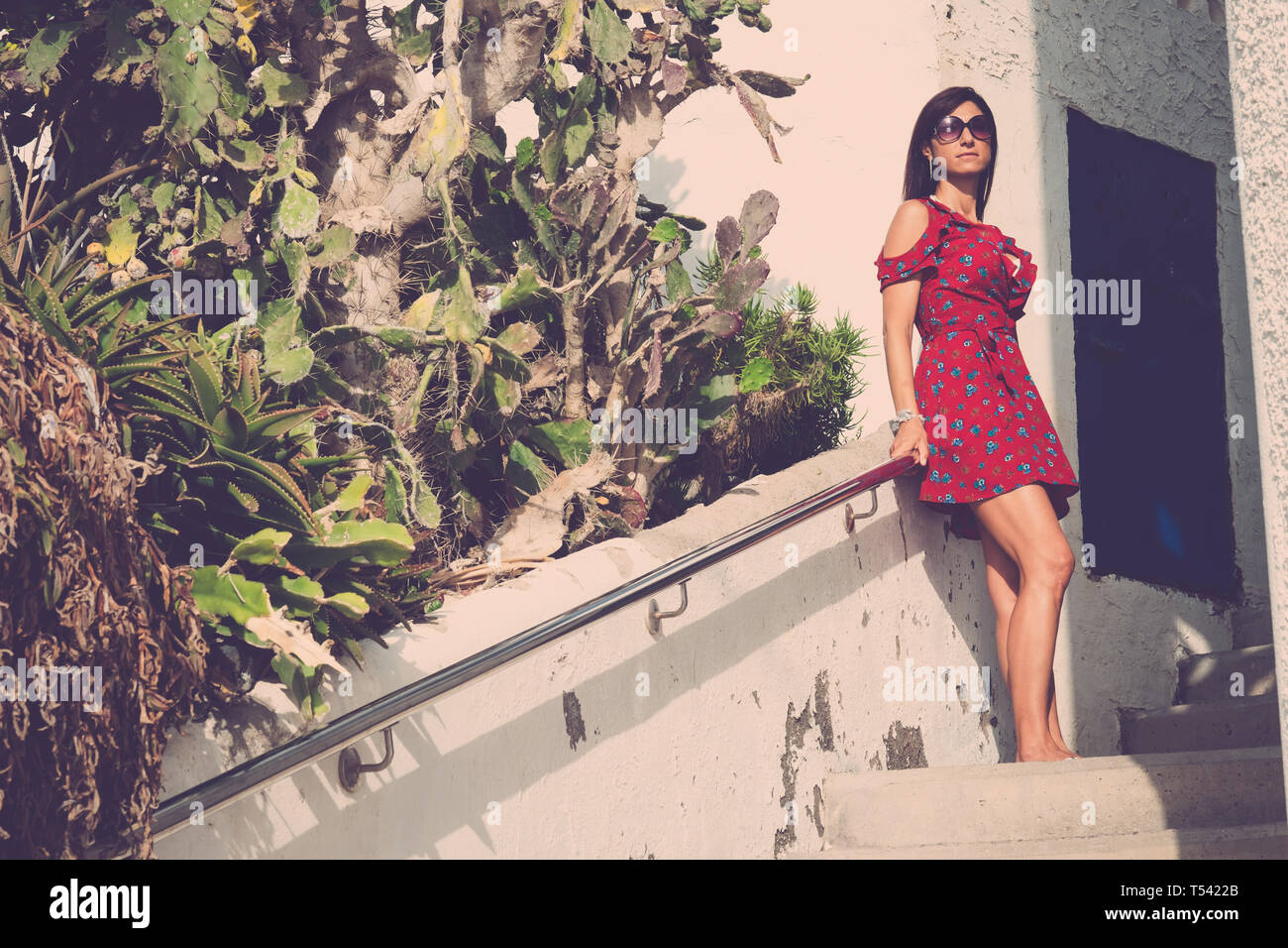Beautiful young caucasian woman in fashion style coloured dress pose and relax - summer style with sunglasses and hat for trendy people outdoor Stock Photo