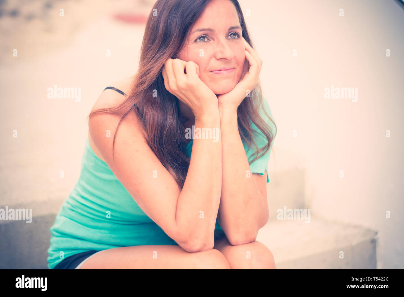 Thoughtful beautiful young woman with black long hair smile kindly whie sit down on a staris - people outdoor in his own thougths - cute caucasian fem Stock Photo