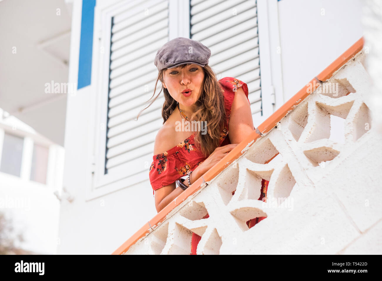 Nice beautiful trendy gitl with hat and red dress sendinkg kiss from a white balcony at home - cute people enjoying life and having fun - tourist and  Stock Photo