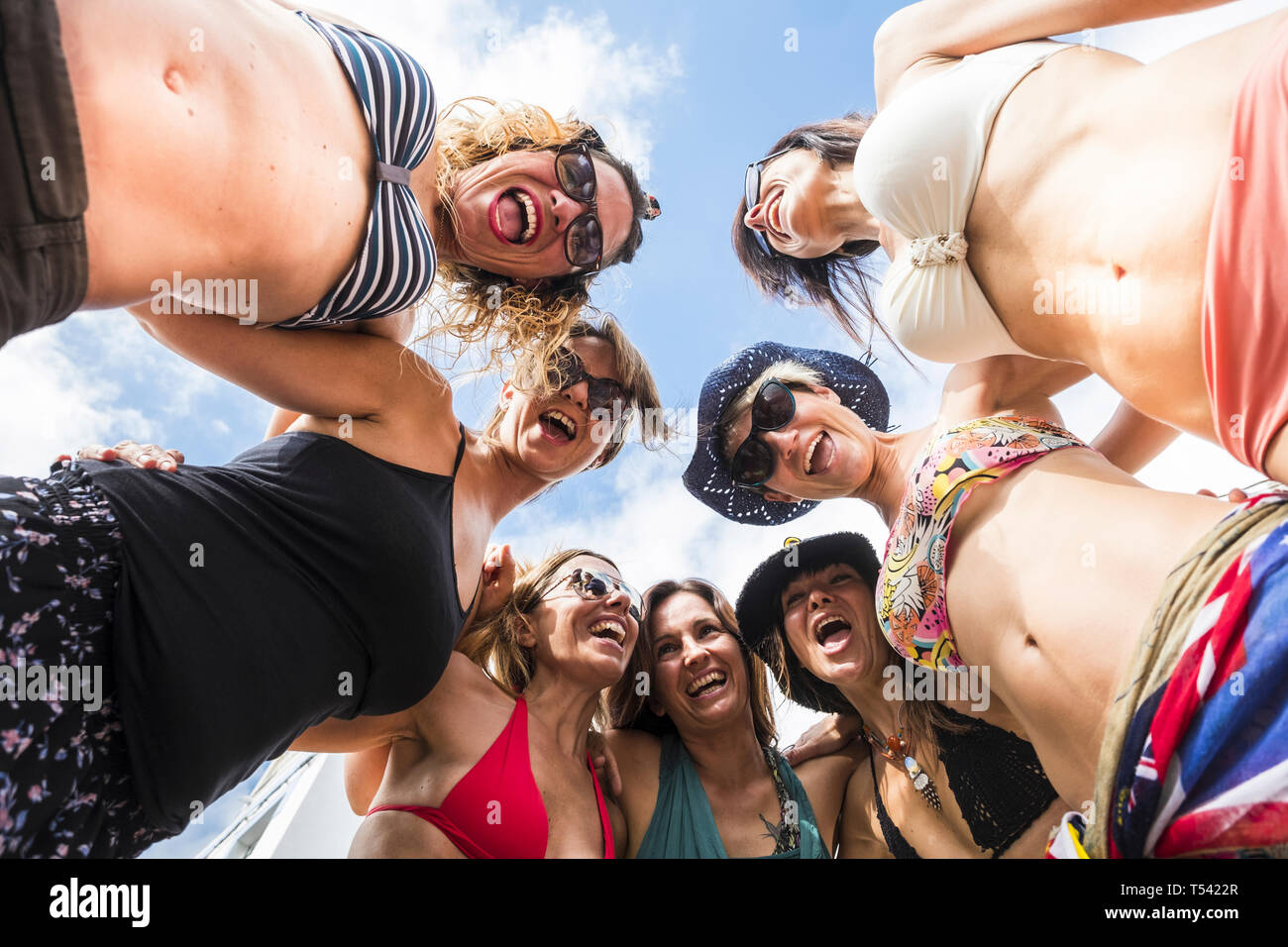 Group of happy cheerful people young friends women together in friendship having fun and laugh hugging and enjoying the sunny day of vacation - crazin Stock Photo