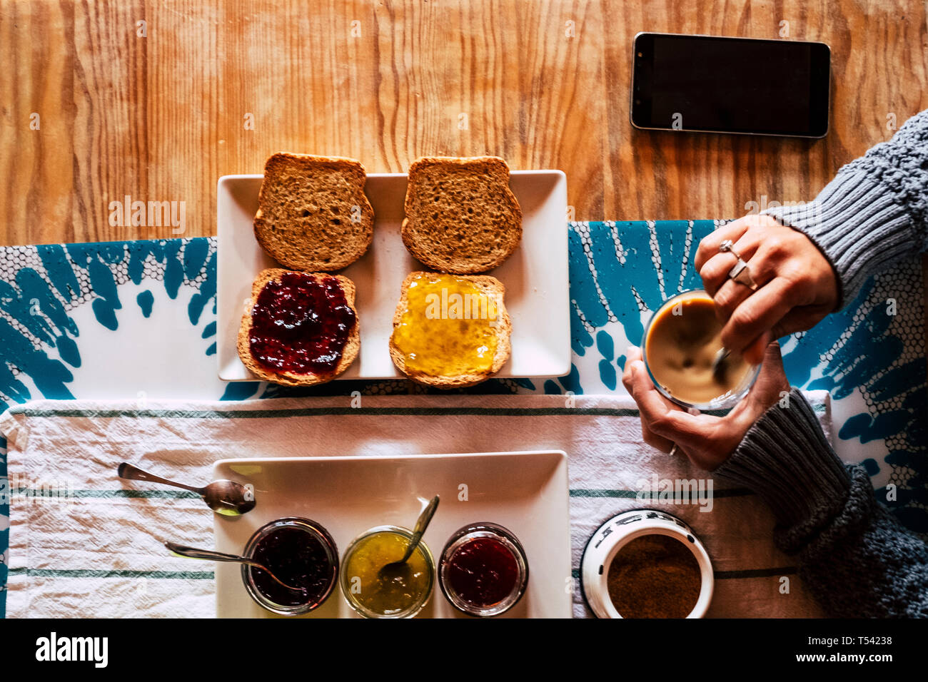 Vertical top point of view of woman doing breakfast in hotel or home - bread and mermalades and coffee time for healthy energy food to start the day - Stock Photo