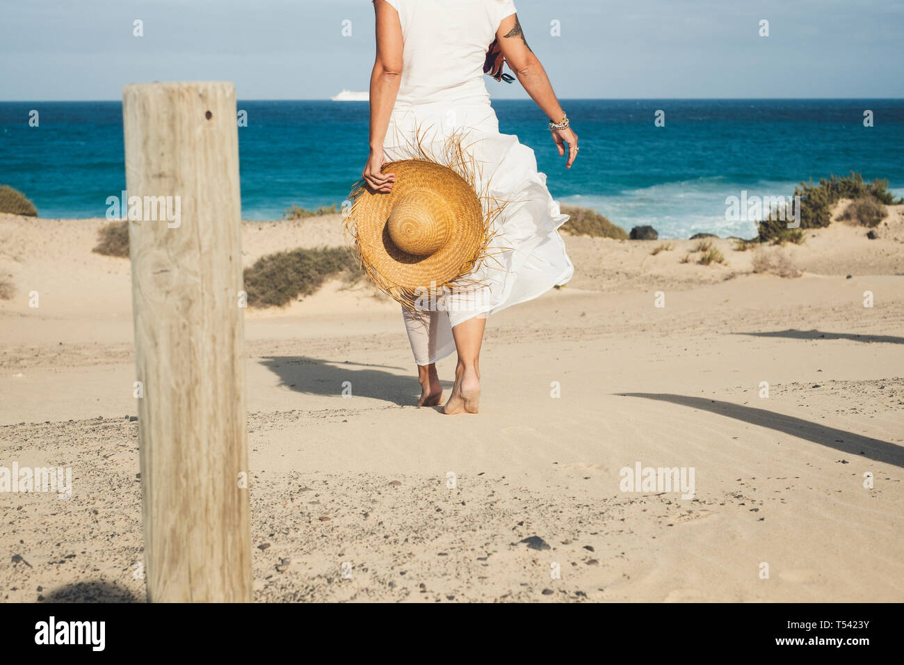 Elegant fashion lady in white dress and natural hat walking to the beach barefoot enjoying the summer holiday vacation day in tropical place - blue se Stock Photo