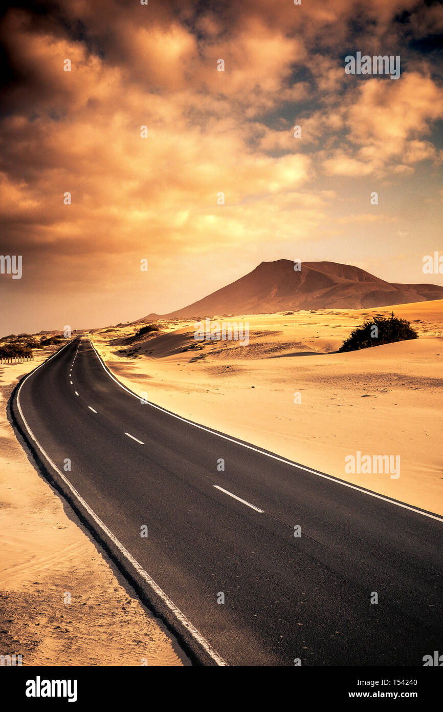 Beautiful black long road for travel conpcept with sand desert dunes on the sides and mountin in the beakcgorund - sunset warm cloudy sky - scenic lan Stock Photo