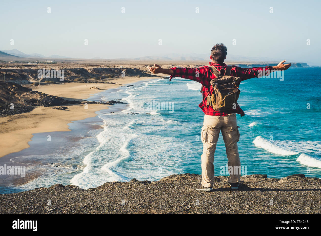Alone happy traveler with backpack people man enjoying the destination place beach standing on a cliff and opening arms for success and joyful concept Stock Photo