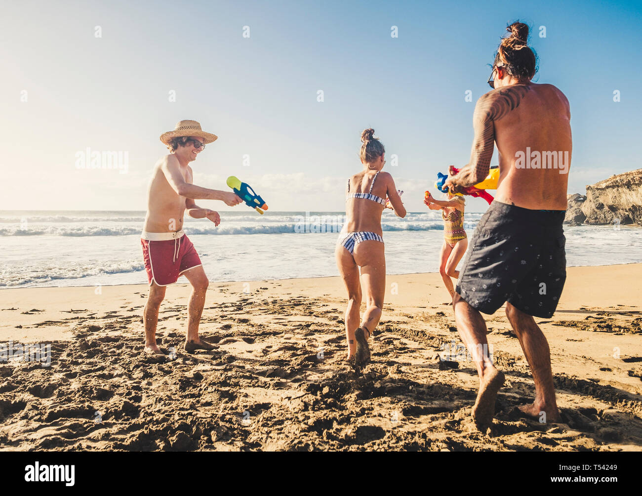 Group of people young caucasian men and women play with water gun at the beach during friends vacation together in outdoor in a sunny day of holiday - Stock Photo