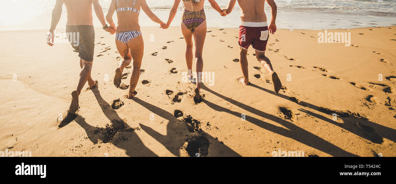 Back view people in summer holiday vacation running on the sand at the beach to the water sea all together in friendship holding hands - bikini group  Stock Photo
