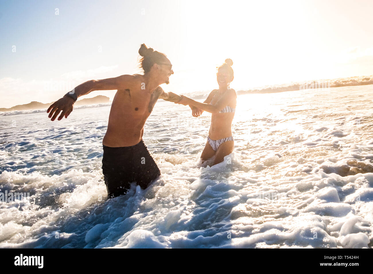 Beautiful caucasian couple enjoy the summer day of vacation with sunlight in background playing and having fun in the sea - people in bikini holiday e Stock Photo