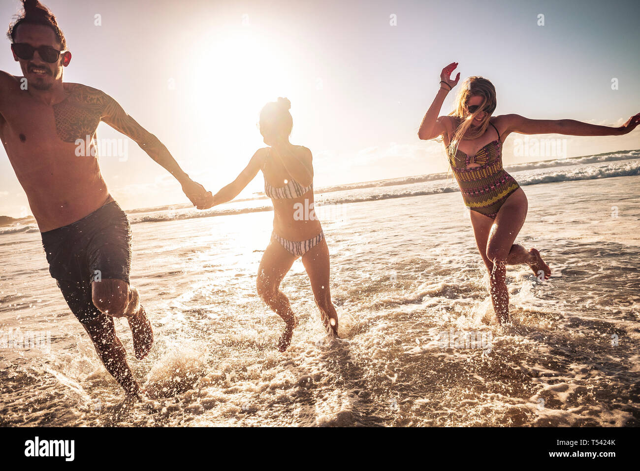Friends caucasian group of people man and two women enjoy and have fun together in friendship during summer vacation running out of the water - sunset Stock Photo