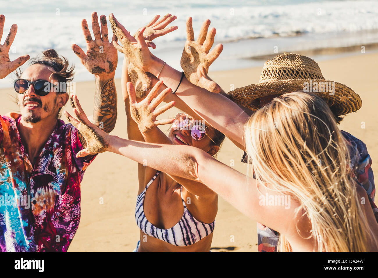 Friends people in summer vacation at the beach show their hands together dirt of sand after a funny day of activity at the sea lifestyle - group men a Stock Photo