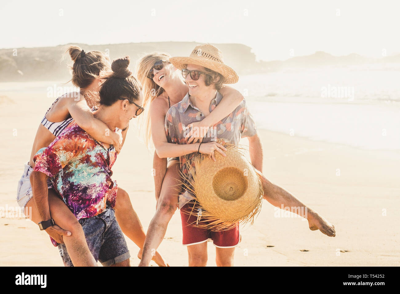 Cheerful friends couple of people girls and boys have fun together at the berach in summer holiday vacation together - men carrying the women and ever Stock Photo