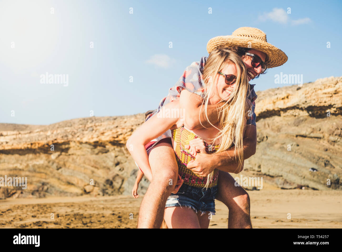 Alternative funny couple have fun together at the beach in sunny day of vacation - girl carry young men on his back and both laugh a lot and enjoy the Stock Photo