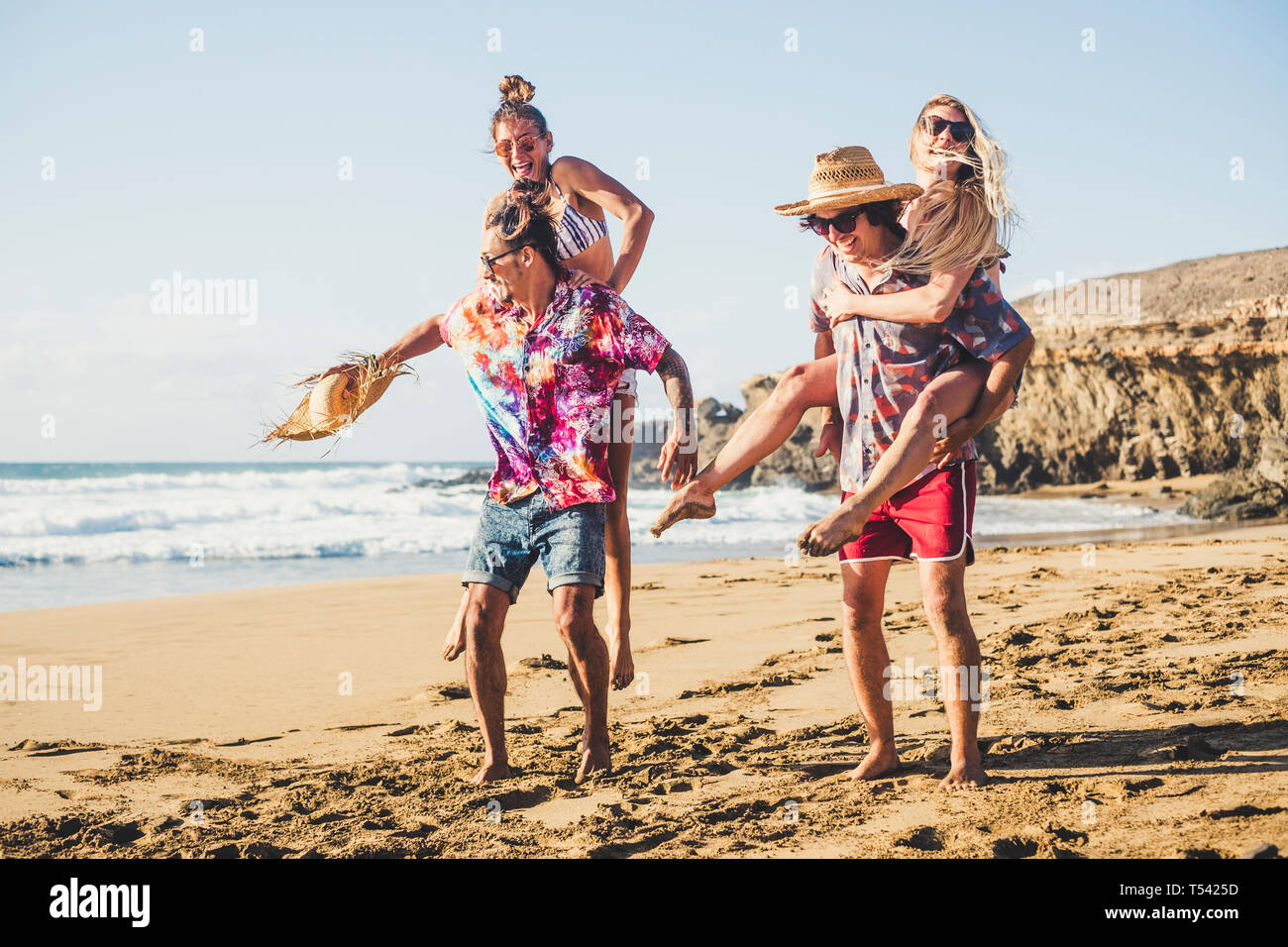 Happy group of people on vaation - youthful and funny concept with young men and women having fun together in friendship playing - boys carrying girls Stock Photo