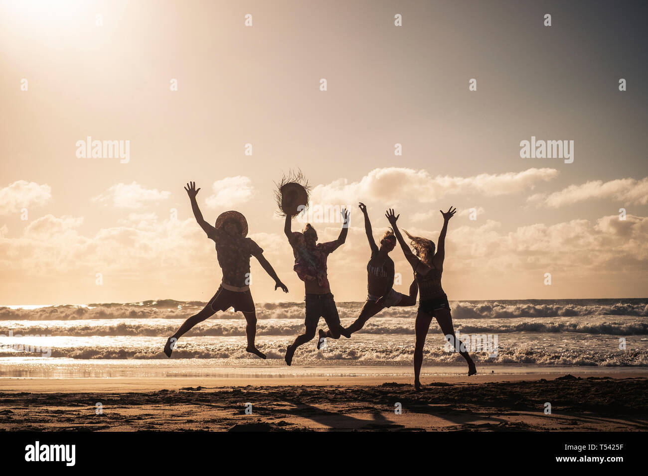 Group of people jump happy together at the beach during sunset with sky in background and silhouette bodies - summer vacation holiday for friends peop Stock Photo