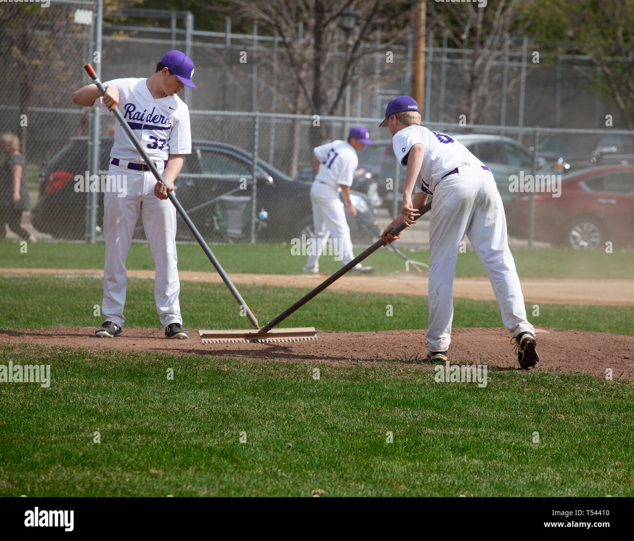 Teenage baseball players raking the bases for the game at Cretin-Derham Hall home field. St Paul Minnesota MN USA - Stock Image