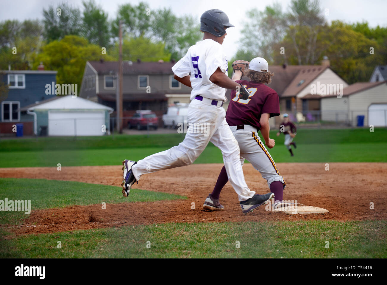 Is he safe or out, as runner tries to beat the throw to first base at Cretin-Derham Hall school home baseball Field? St Paul Minnesota MN USA - Stock Image