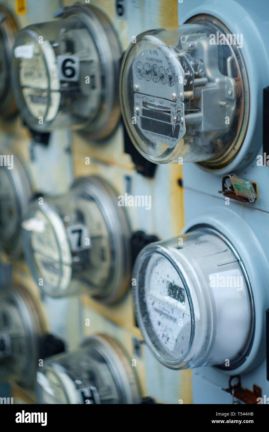 Electric meters measuring usage outside apartment building - Stock Image