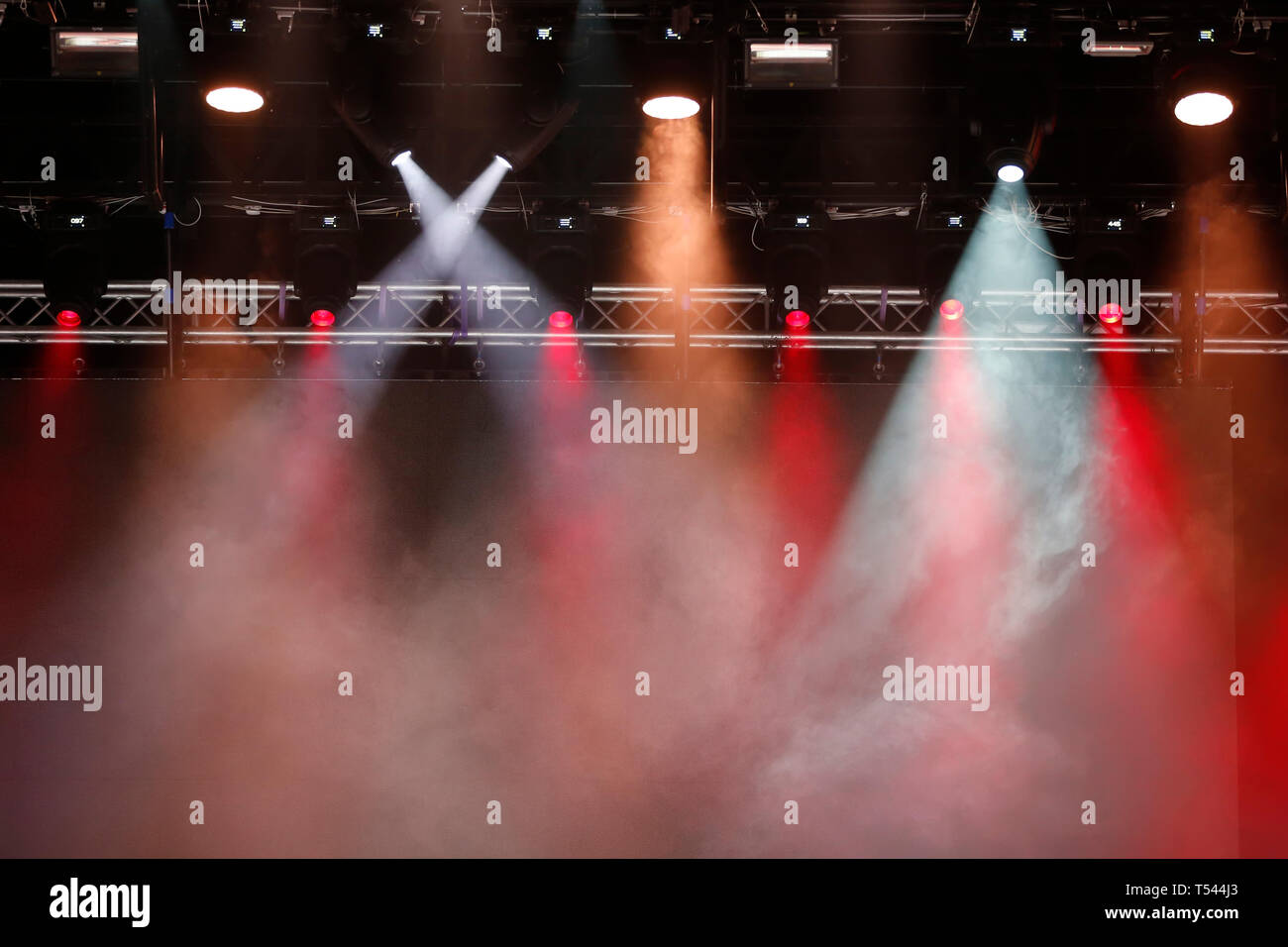 Concert spotlights.Concert spotlights.Red and white rays of powerful projectors on stage - Stock Image