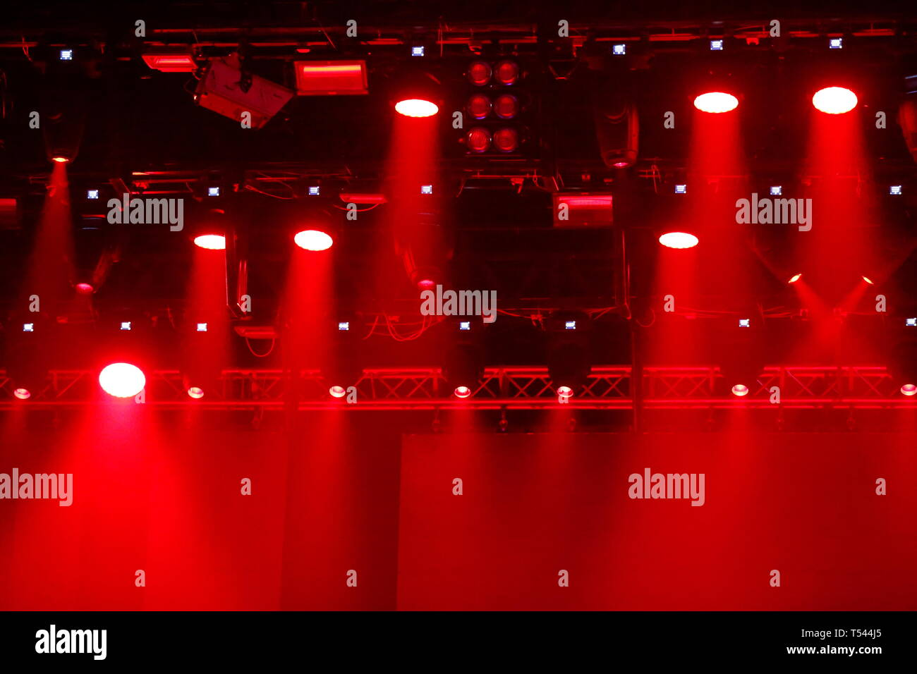 Concert spotlights.Red and white rays of powerful projectors on stage - Stock Image
