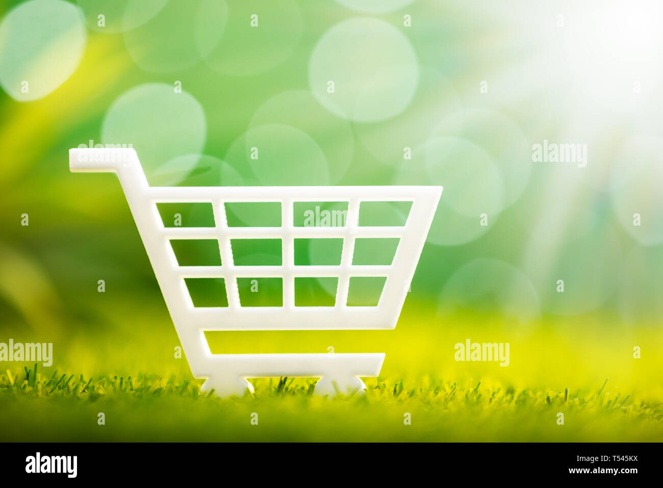 Close-up Of White Shopping Cart On Green Grass Stock Photo