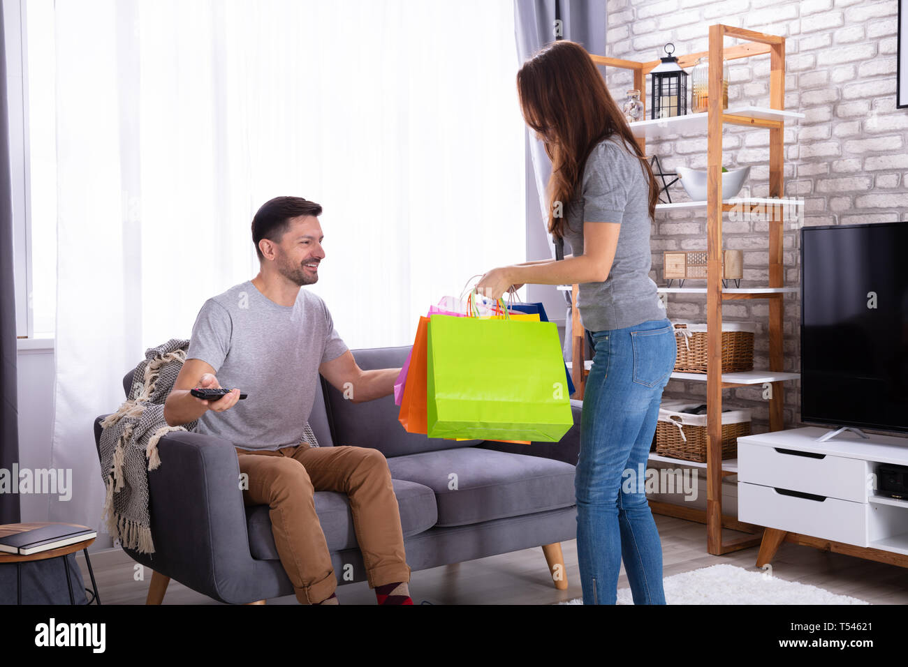 Happy Husband Sitting On Couch Looking At His Wife Carrying Shopping Bags - Stock Image
