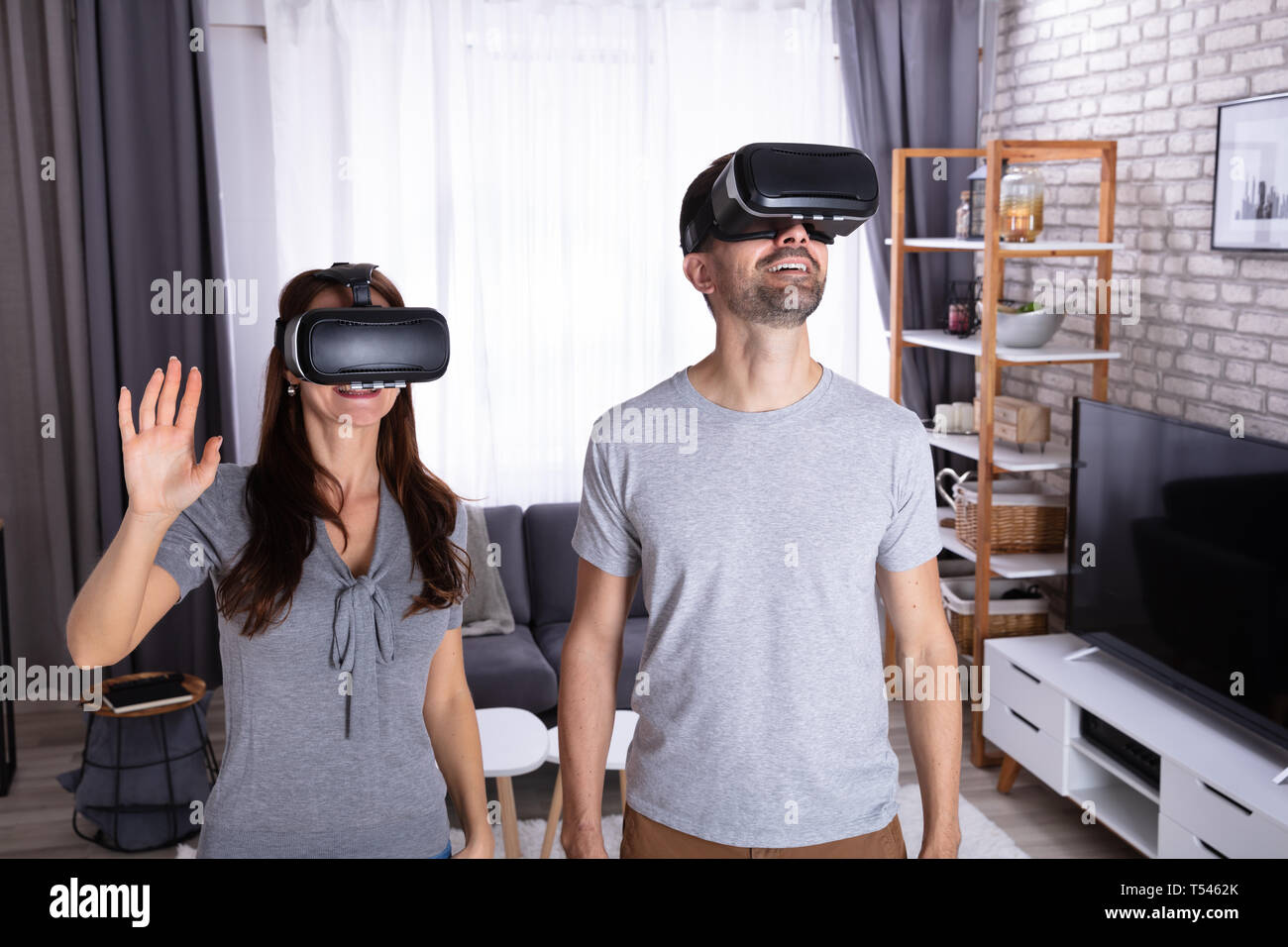 Young Couple Sitting On Sofa Experiencing Virtual Reality Headset - Stock Image